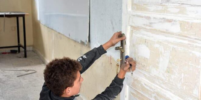 صورة طفل يُصلح باب مدرسة تفتح باب الانتقاد على مسؤولين في اللاذقية